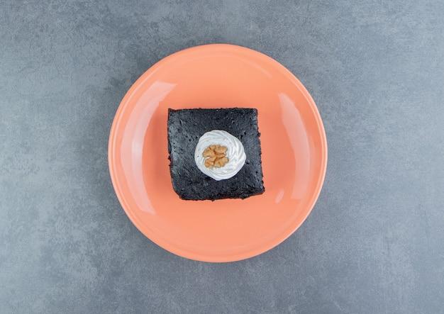Fatia de bolo de brownie no prato laranja.