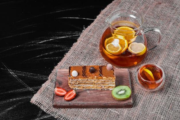 Fatia de bolo de caramelo em uma travessa de madeira.