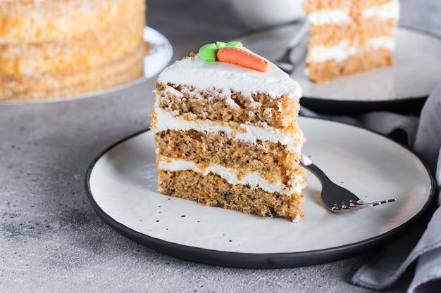 Fatia de bolo de cenoura caseiro com cobertura de creme de queijo no prato no fundo da mesa de pedra cinza