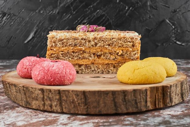 Fatia de bolo de cenoura com biscoitos em uma placa de madeira.