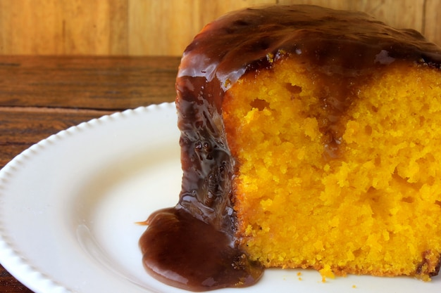 Fatia de bolo de cenoura com cobertura de chocolate na placa cerâmica branca