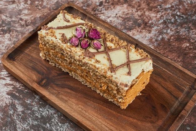 Fatia de bolo de cenoura em uma placa de madeira.