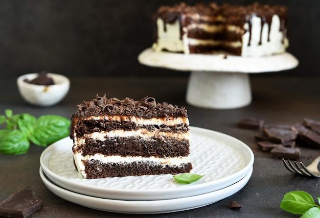 Fatia de bolo de chocolate. bolo de trufa de chocolate com cream cheese em um fundo escuro.