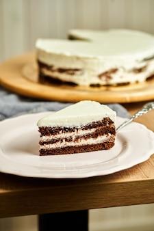Fatia de bolo de chocolate caseiro no prato. fundo de madeira