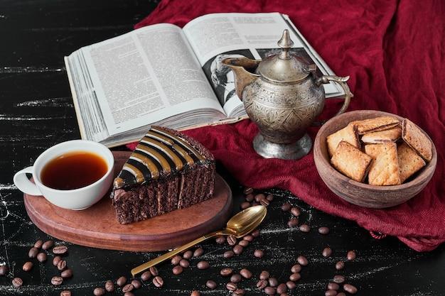 Fatia de bolo de chocolate com biscoitos e uma xícara de chá.