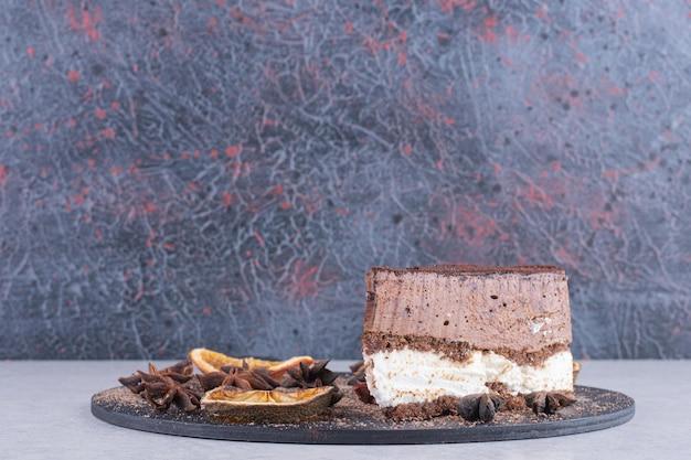 Fatia de bolo de chocolate com cravo e rodelas de laranja no prato escuro.