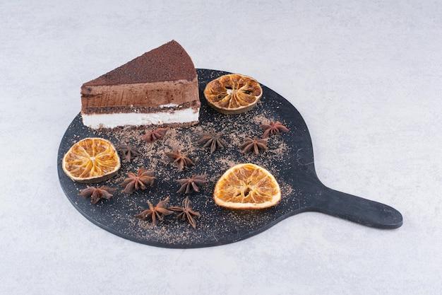 Fatia de bolo de chocolate com cravo e rodelas de laranja no tabuleiro escuro. foto de alta qualidade