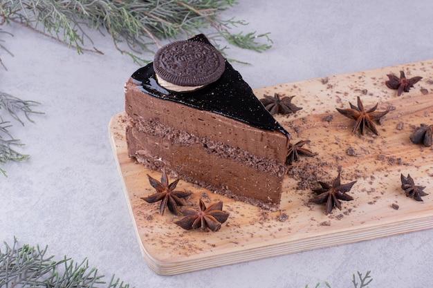 Fatia de bolo de chocolate com cravo na placa de madeira. foto de alta qualidade