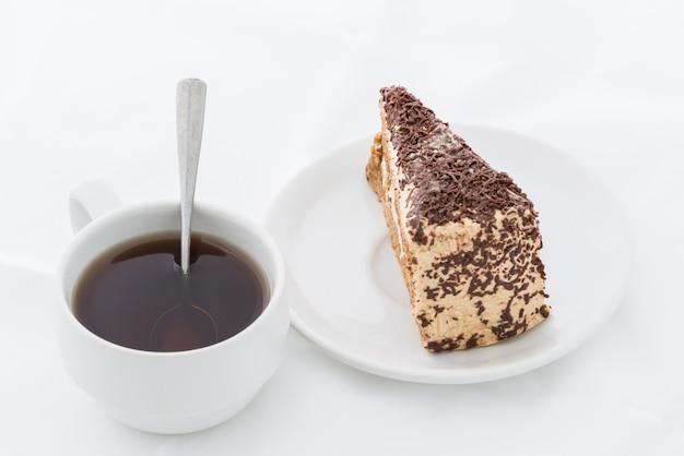 Fatia de bolo de chocolate com curl no prato branco com bebida quente