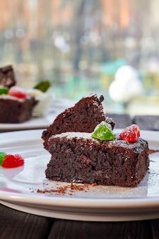 Fatia de bolo de chocolate com hortelã e sorvete de frutas cristalizadas em um prato branco