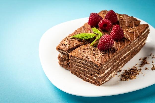 Fatia de bolo de chocolate com recheio de leite e framboesa na chapa branca na superfície azul.