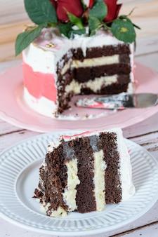 Fatia de bolo de chocolate com recheio de mascarpone. no fundo desfocado, bolo coberto com creme de manteiga de merengue suíço.