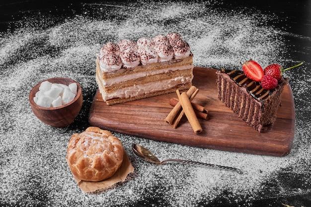 Fatia de bolo de chocolate com tiramisu em uma travessa de madeira.