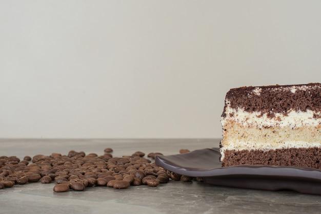 Fatia de bolo de chocolate e grãos de café na mesa de mármore.