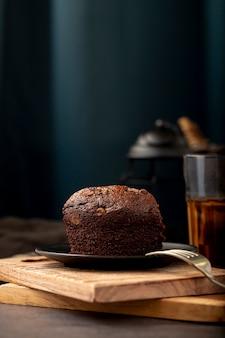 Fatia de bolo de chocolate em um suporte de madeira