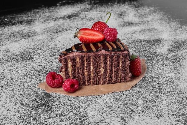 Fatia de bolo de chocolate em uma travessa de madeira.