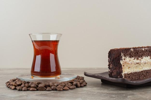 Fatia de bolo de chocolate, grãos de café e copo de chá na mesa de mármore.