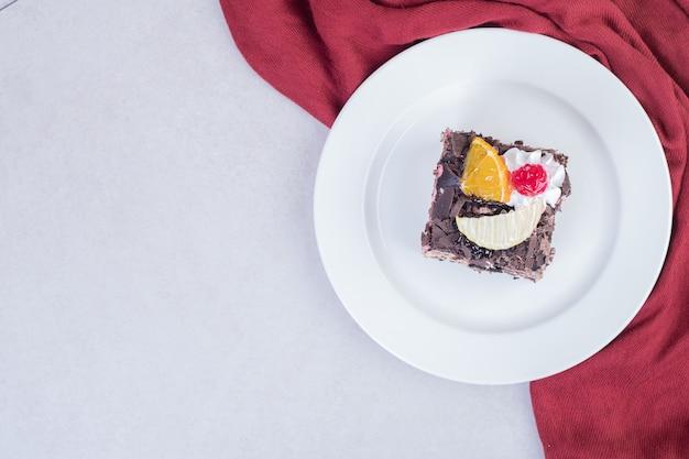 Fatia de bolo de chocolate na chapa branca com toalha de mesa vermelha.