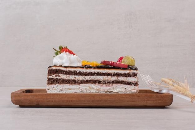 Fatia de bolo de chocolate na placa de madeira com fatias de frutas.