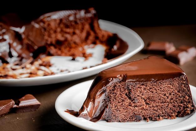 Fatia de bolo de chocolate no prato branco sobre a mesa