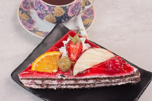 Fatia de bolo de chocolate no prato com fatias de frutas e uma xícara de chá.