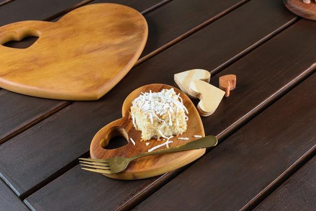 Fatia de bolo de coco em um prato de madeira em forma de coração.