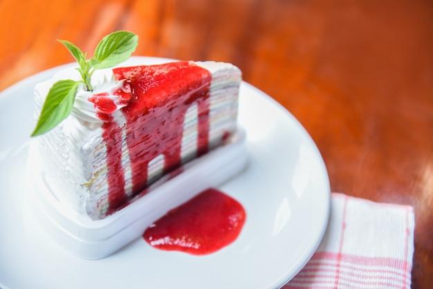 Fatia de bolo de crepe com molho de morango na chapa branca na mesa / arco-íris de pedaço de bolo