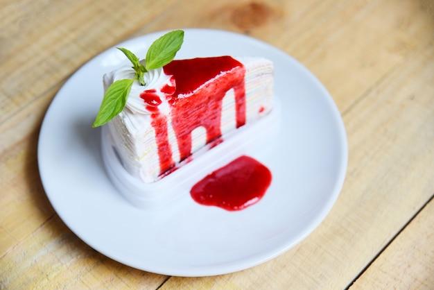 Fatia de bolo de crepe com molho de morango na chapa branca