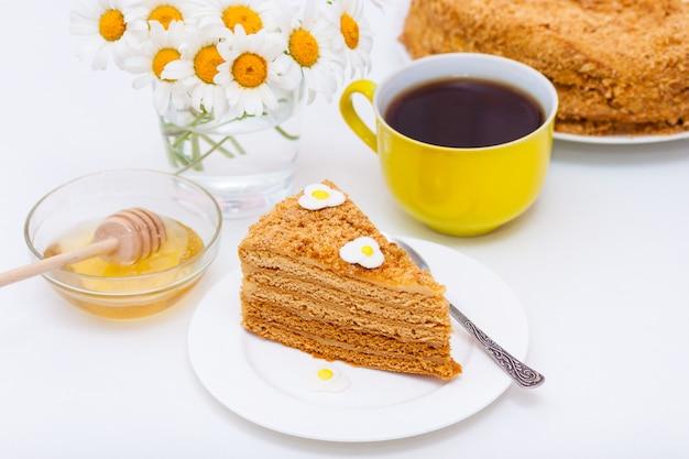 Fatia de bolo de mel caseiro das camadas com o copo amarelo do chá ou o café e as camomilas.