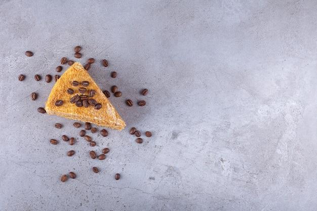 Fatia de bolo de mel em camadas com grãos de café colocados em uma pedra.