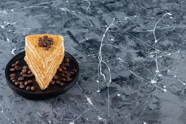 Fatia de bolo de mel em camadas com grãos de café colocados sobre uma mesa de mármore.