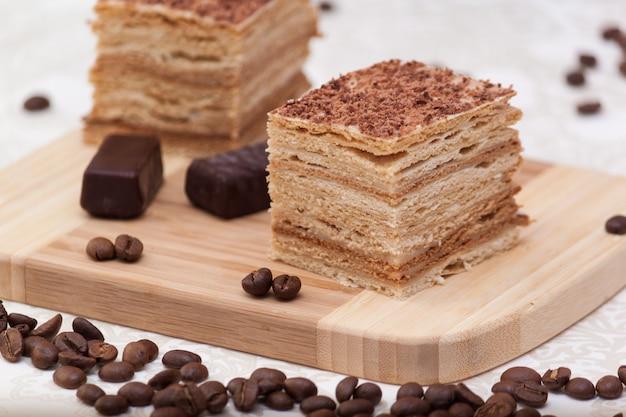 Fatia de bolo de mel em camadas com grãos de café, doces e copo preto, foco seletivo