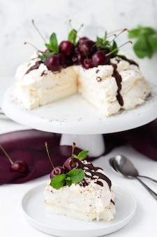Fatia de bolo de pavlova com cobertura de chocolate e cerejas sobre um fundo branco