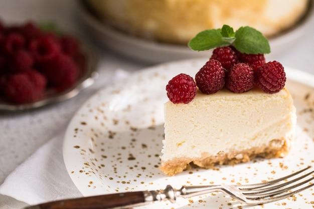 Fatia de bolo de queijo clássico de new york com as framboesas na placa branca. closeup vista. padaria em casa