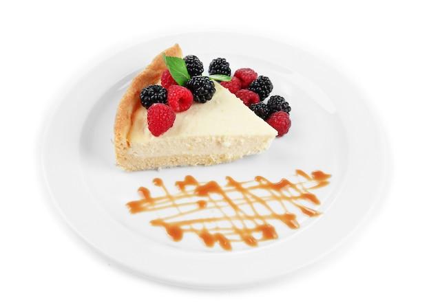 Fatia de bolo de queijo com frutas vermelhas e molho no prato, d no branco