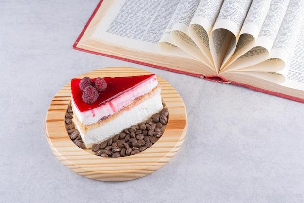 Fatia de bolo de queijo com grãos de café e livro.