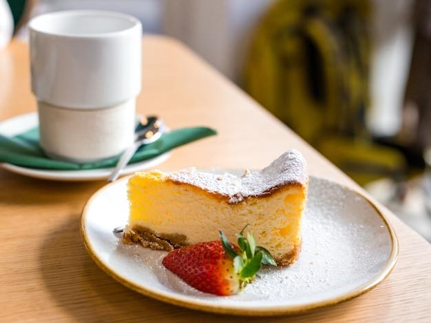 Fatia de bolo de queijo com morango em fundo marrom, foco seletivo. um cheesecake e café