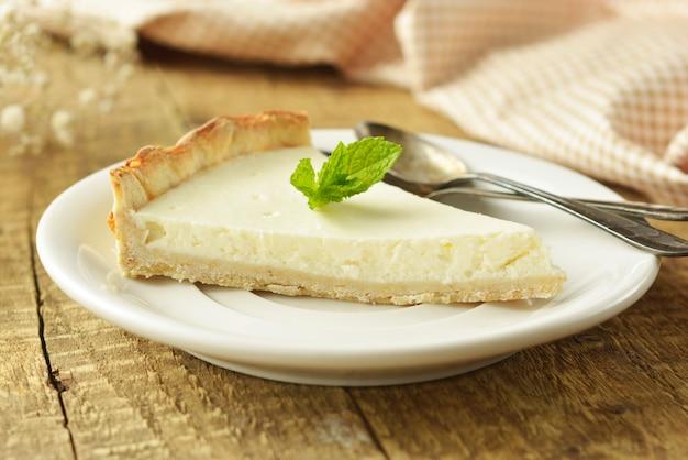 Fatia de bolo de queijo na mesa de madeira. sobremesa caseira.