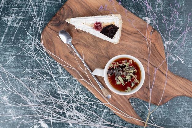 Fatia de bolo de queijo na placa de madeira com uma xícara de chá. foto de alta qualidade