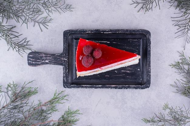 Fatia de bolo de queijo no quadro negro com galho de pinheiro. foto de alta qualidade