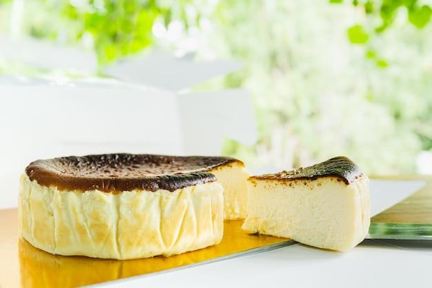 Fatia de bolo de queijo queimado basco caseiro na mesa branca.