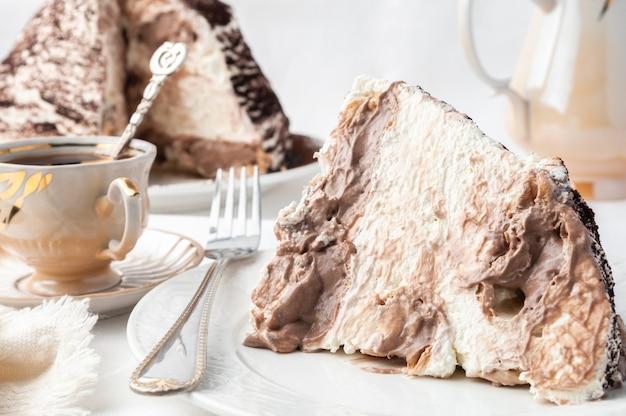 Fatia de bolo de tiramassu em um prato branco feito em casa perto de um garfo e uma xícara de café no fundo está um prato com bolo e uma cafeteira fundo branco close up