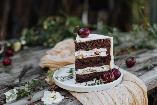 Fatia de bolo decorado com cereja em uma mesa de madeira