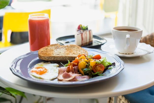 Fatia de bolo delicioso; café da manhã; xícara de café e batido servido na mesa