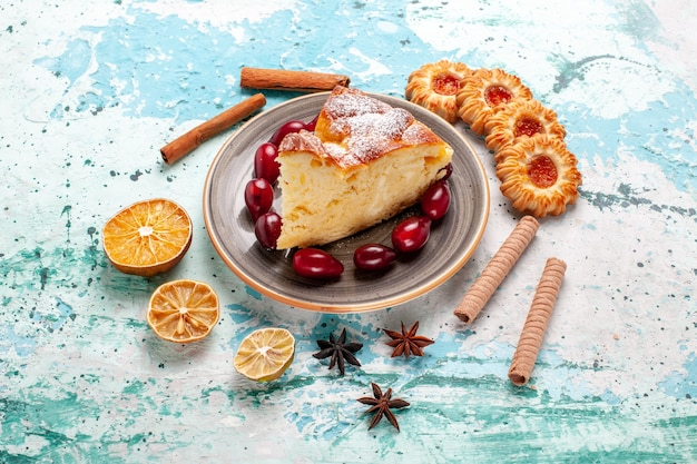 Fatia de bolo delicioso com biscoitos na superfície azul de vista frontal