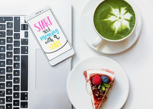 Fatia de bolo delicioso; xícara de chá matcha e telefone móvel com mensagem no laptop sobre a mesa