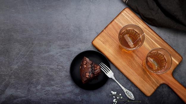 Fatia de bolo e xícaras de chá em um suporte de madeira em um terreno de volta cinza
