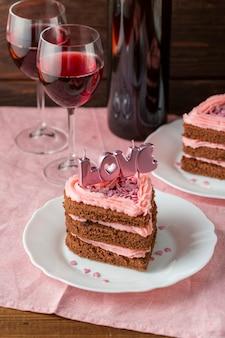 Fatia de bolo em forma de coração com taças de vinho e velas