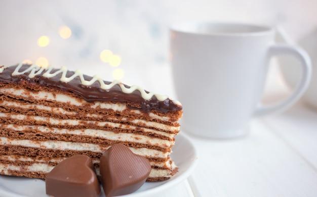 Fatia de bolo em um pires e corações em um fundo branco