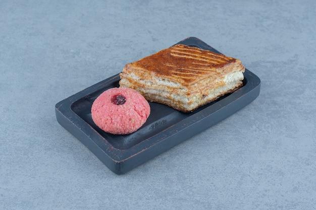 Fatia de bolo fresco com biscoito rosa na placa de madeira.